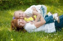 Una chica joven con el mather en una hierba verde Fotografía de archivo