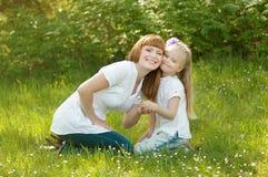 Una chica joven con el mather en una hierba verde Imagen de archivo libre de regalías