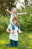 Una chica joven con el mather en una hierba verde Foto de archivo