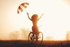 Una chica joven con el montar a caballo del paraguas en una bici Fotografía de archivo