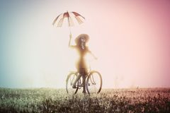 Una chica joven con el montar a caballo del paraguas en una bici Fotografía de archivo libre de regalías
