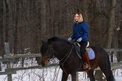 Una chica joven con el pelo blanco aprende montar un caballo La muchacha comenzada recientemente para practicar equestrianism La  imágenes de archivo libres de regalías