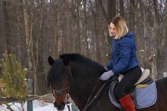 Una chica joven con el pelo blanco aprende montar un caballo La muchacha comenzada recientemente para practicar equestrianism La  imagen de archivo libre de regalías