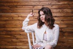 Una chica joven con el pelo largo, la ropa blanca, en una silla y un fondo de madera Fotos de archivo libres de regalías