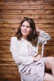 Una chica joven con el pelo largo, la ropa blanca, en una silla y un fondo de madera Fotos de archivo