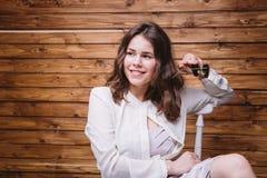 Una chica joven con el pelo largo, la ropa blanca, en una silla y un fondo de madera Foto de archivo libre de regalías