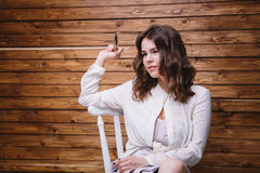 Una chica joven con el pelo largo, la ropa blanca, en una silla y un fondo de madera Foto de archivo
