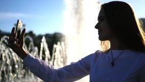 Una chica joven con el pelo largo presenta en la cámara, toma una foto cerca de la fuente en la ciudad, con el efecto de una lent almacen de video