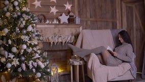 Una chica joven con el pelo oscuro largo está leyendo un libro mientras que se sienta en una butaca cerca de un árbol de navidad  metrajes