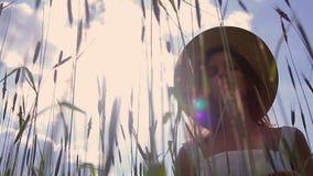 Una chica joven con el pelo oscuro largo que se coloca en un campo verde almacen de metraje de vídeo