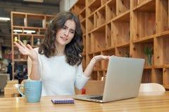 Una chica joven con el pelo rizado largo que se sienta en un café con un lapto Imagen de archivo