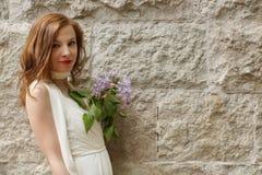 Una chica joven con el pelo rojo en un vestido blanco se coloca cerca de una pared de la piedra caliza y sostiene una ramita de l Foto de archivo