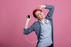 Una chica joven con el pelo rojo es baile, escuchando la música en los auriculares Imagen de archivo