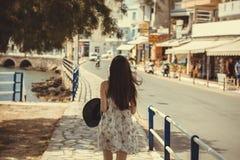 Una chica joven con el sombrero negro en su mano camina a lo largo del muelle de la ciudad de Rethymno, Grecia Chica joven en un  Imagen de archivo