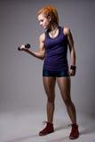 Una chica joven con los dreadlocks que entrena con pesas de gimnasia Fotografía de archivo