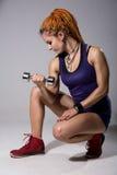Una chica joven con los dreadlocks que entrena con pesas de gimnasia Foto de archivo libre de regalías