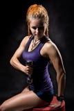 Una chica joven con los dreadlocks que entrena con pesas de gimnasia Fotos de archivo libres de regalías