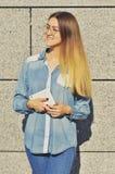 Una chica joven con los vidrios que está llevando una camisa del dril de algodón, sosteniendo una tableta y mirando en la distanc fotografía de archivo