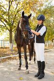 Una chica joven, con un caballo colocándose en crecimiento completo en el aire fresco Fotografía de archivo libre de regalías