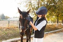 Una chica joven, con un caballo colocándose en el aire abierto, inclinando su cabeza Fotos de archivo