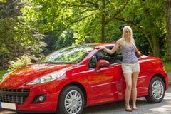 Una chica joven con un coche rojo Fotos de archivo libres de regalías