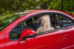 Una chica joven con un coche rojo Imagenes de archivo