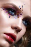 Una chica joven con un corte de pelo corto y un maquillaje creativo brillante Un modelo hermoso con las chispas en cara y los lab Imagen de archivo