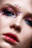 Una chica joven con un corte de pelo corto y un maquillaje creativo brillante Un modelo hermoso con las chispas en cara y los lab Imagen de archivo libre de regalías