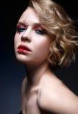 Una chica joven con un corte de pelo corto y un maquillaje creativo brillante Un modelo hermoso con las chispas en cara y los lab Fotos de archivo