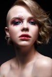 Una chica joven con un corte de pelo corto y un maquillaje creativo brillante Un modelo hermoso con las chispas en cara y los lab Fotos de archivo libres de regalías