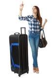 Una chica joven con un grande, ennegrece el bolso en las ruedas, calendario del viaje de las miradas en una estación. Foto de archivo libre de regalías