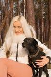 Una chica joven con un perro en el bosque Fotos de archivo libres de regalías