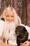 Una chica joven con un perro en el bosque Fotografía de archivo libre de regalías
