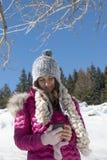 Una chica joven con un smartphone en las montañas en invierno Imagen de archivo