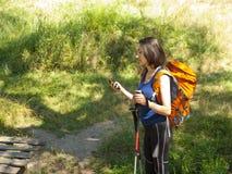Una chica joven con un uso de la mochila el teléfono Imagen de archivo
