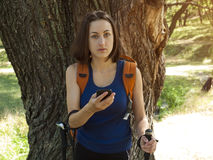 Una chica joven con un uso de la mochila el teléfono Fotografía de archivo