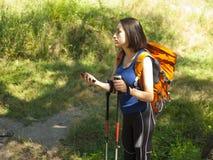 Una chica joven con un uso de la mochila el teléfono Imágenes de archivo libres de regalías