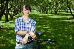 Una chica joven con una bicicleta en el parque Fotos de archivo