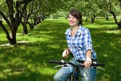 Una chica joven con una bicicleta en el parque Fotos de archivo libres de regalías