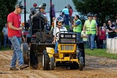 Una chica joven conduce en un tirón del tractor del césped imagen de archivo libre de regalías
