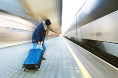 Una chica joven corre a lo largo de la plataforma con una maleta grande, es atrasada para el tren ?ltimo concepto fotografía de archivo