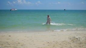 Una chica joven corre a lo largo de la playa, creando un espray del agua Isla tropical, en un día caliente metrajes