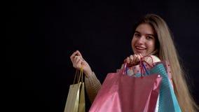 Una chica joven del aspecto caucásico con una misma clase del radosnym de lanza encima de sus manos llenas de bolsos, compras, a almacen de video
