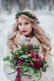 Una chica joven del aspecto eslavo con una guirnalda de wildflowers La novia hermosa sostiene un ramo en fondo del invierno fotografía de archivo