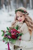 Una chica joven del aspecto eslavo con una guirnalda de wildflowers La novia hermosa sostiene un ramo en fondo del invierno fotografía de archivo libre de regalías