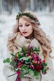 Una chica joven del aspecto eslavo con una guirnalda de wildflowers La novia hermosa sostiene un ramo en fondo del invierno foto de archivo