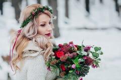 Una chica joven del aspecto eslavo con una guirnalda de wildflowers La novia hermosa sostiene un ramo en fondo del invierno imagen de archivo