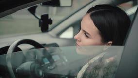 Una chica joven detrás de la rueda de un coche baja la puerta de la ventana del coche metrajes