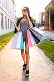 Una chica joven disfruta de compras acertadas, en el fondo de fotos de archivo