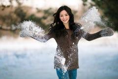 Una chica joven divertida en un suéter lanza para arriba una nieve Fotografía de archivo libre de regalías